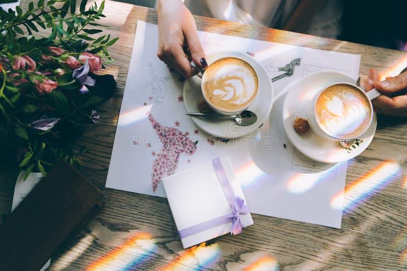 Händer av bruden och brudgummen för en kopp kaffe Bröllopbukett på bordlägga royaltyfri foto
