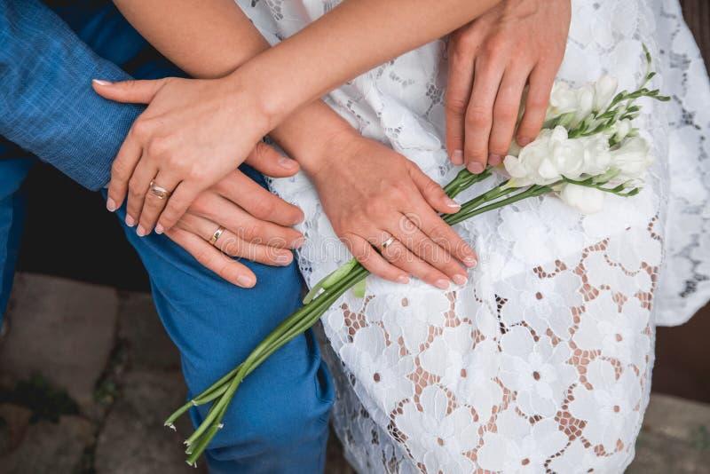 Händer av bruden och brudgummen ligger på en bukett av blommor övre sikt bröllop arkivbild