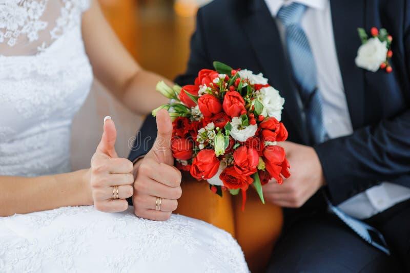 Händer av bruden och brudgummen på bakgrunden av en bröllopbouq royaltyfria bilder