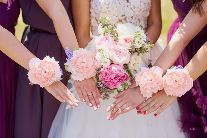 Händer av bruden och flickvännen med dekorativa blommor arkivfoton