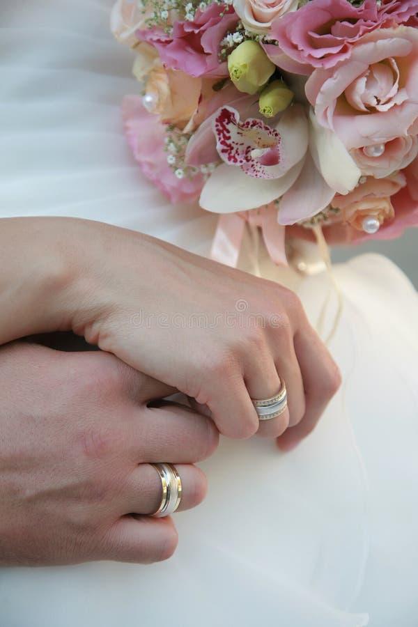 Händer av brudgummen och bruden royaltyfri bild