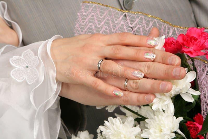 Händer av brudgummen och bruden arkivfoton