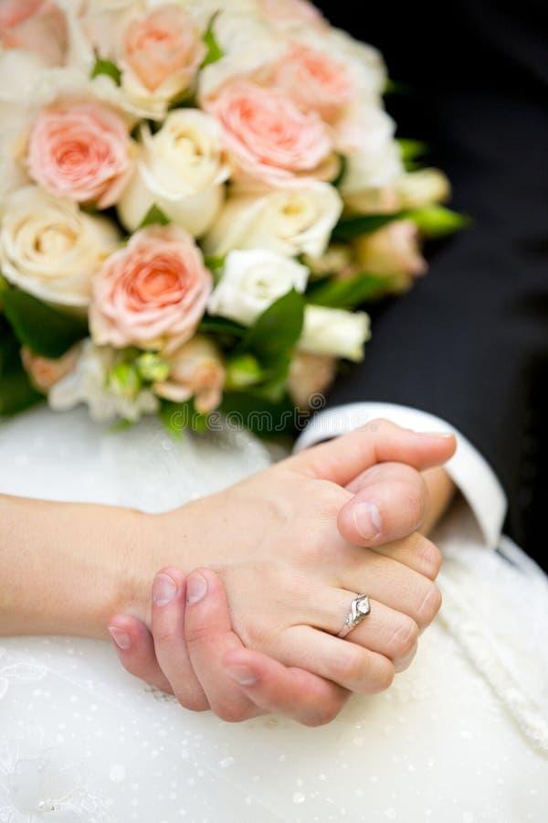 Händer av brudgummen och bruden med förlovningsring- och bröllopbuketten arkivfoto