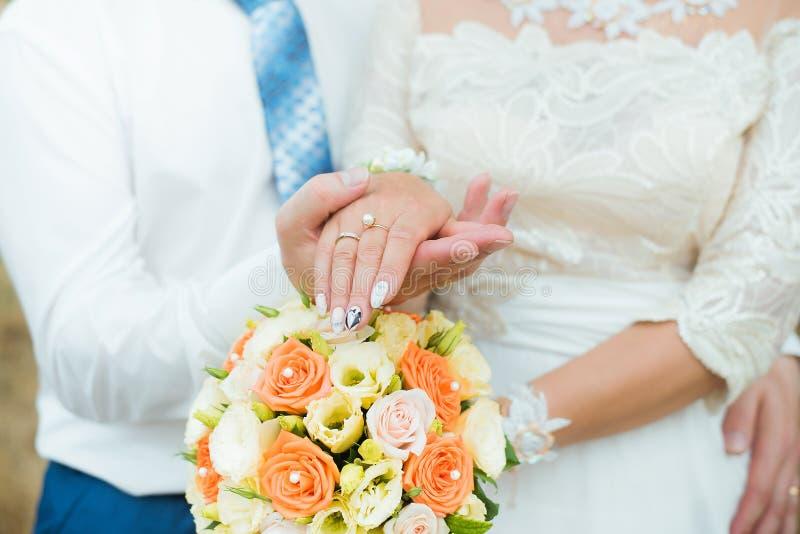 Händer av brudgummen och bruden med vigselringar och blommarosor Begrepp av f?r?lskelse och f?rbindelsen arkivbilder