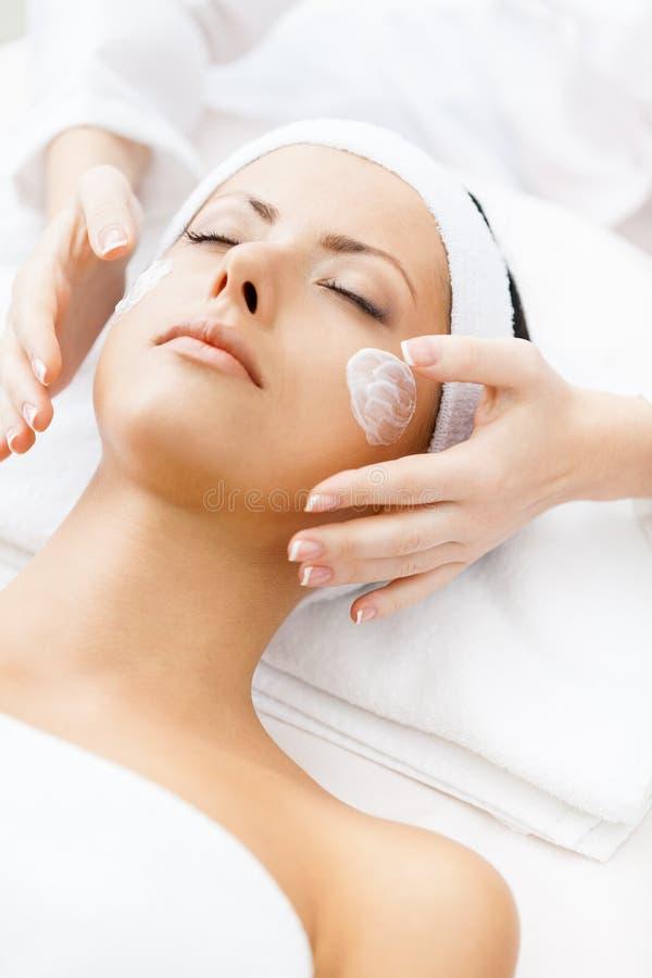 Händer av cosmetologisten applicerar kräm till flickaframsidan arkivfoto