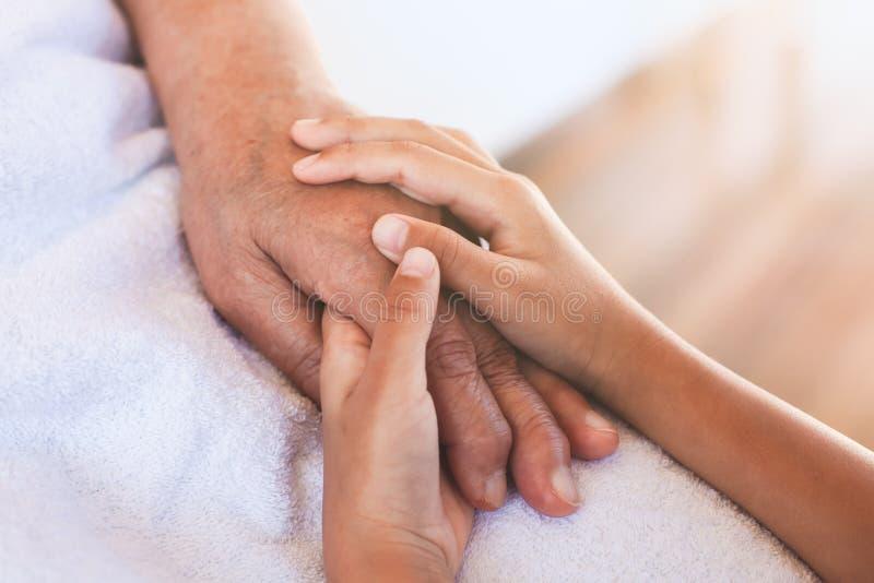 Händer av den asiatiska barnflickan som rymmer rynkig hud för äldre morförälderhänder royaltyfri bild