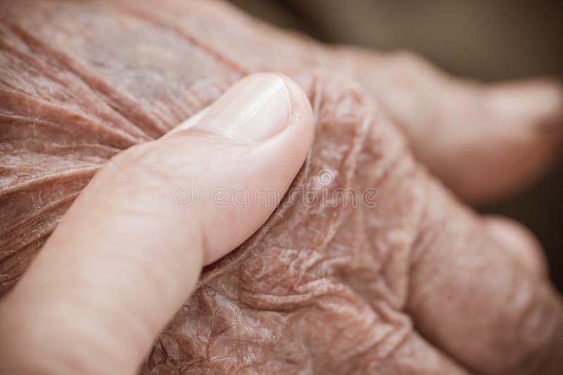 Händer av den asiatiska kvinnan som rymmer fattiga äldre farfarmanhänder, rynkade hud med mening ta omsorg av förälskelse Världsv arkivbilder
