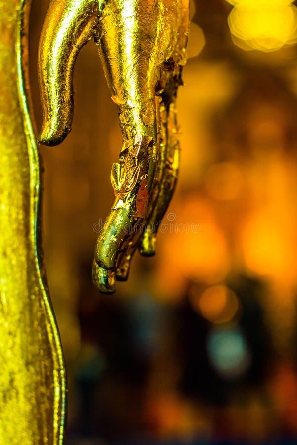 Händer av den guld- Buddhastatyn arkivfoton