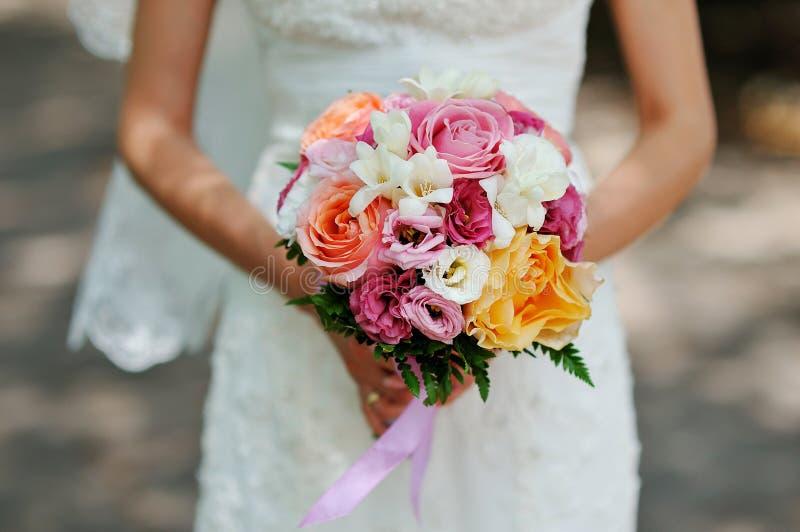 Händer av den härliga bröllopbuketten för brud royaltyfri fotografi