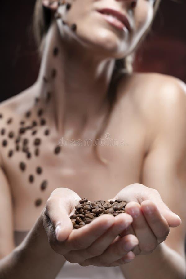 Händer av den härliga le flickan med nakna skuldror som rymmer kaffebönor Bönor som klibbas artistically till sund ren hud av arkivbild