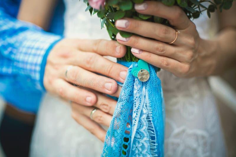 Händer av den hållande bruden för brudgum med bröllopbuketten arkivbild