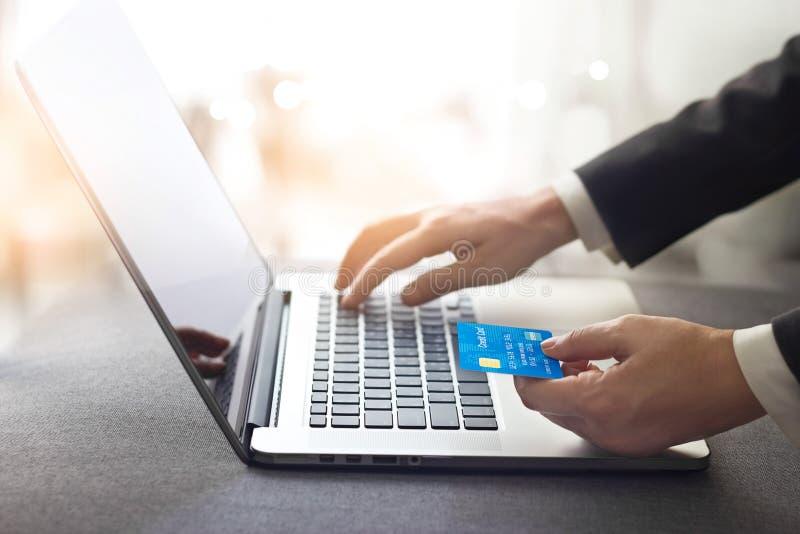 Händer av den hållande kreditkorten för affärsman och användabärbara datorn, onlin royaltyfri bild