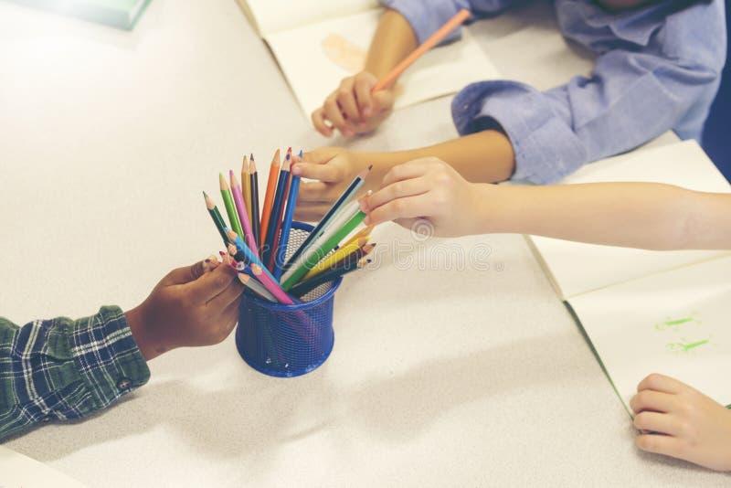 Händer av den hackan för litet barn kulöra blyertspennor på tabellen, teckning för litet barn med kulöra blyertspennor Idérik sti arkivfoto