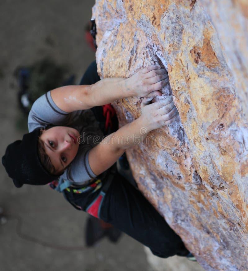 Händer av den kvinnliga klättraren som rymmer kanten arkivbild