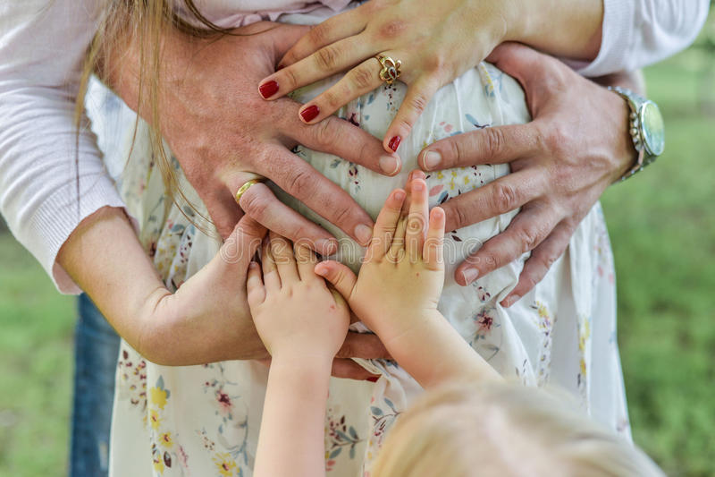 Händer av den kvinnliga mannen och behandla som ett barn gör hjärtaform det gulliga tecknet på den kala buken av gravid kvinnamod arkivfoton