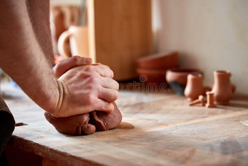 Händer av den manliga keramikern som gjuter en lera i krukmakeriseminariet, närbild, selektiv fokus arkivfoto