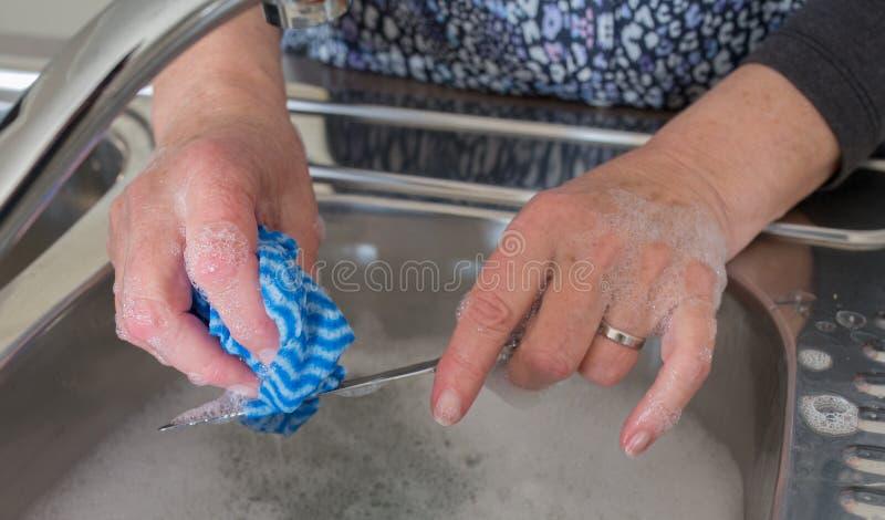 Händer av den medelåldersa kvinnan som tvättar en kniv på diskhon fotografering för bildbyråer