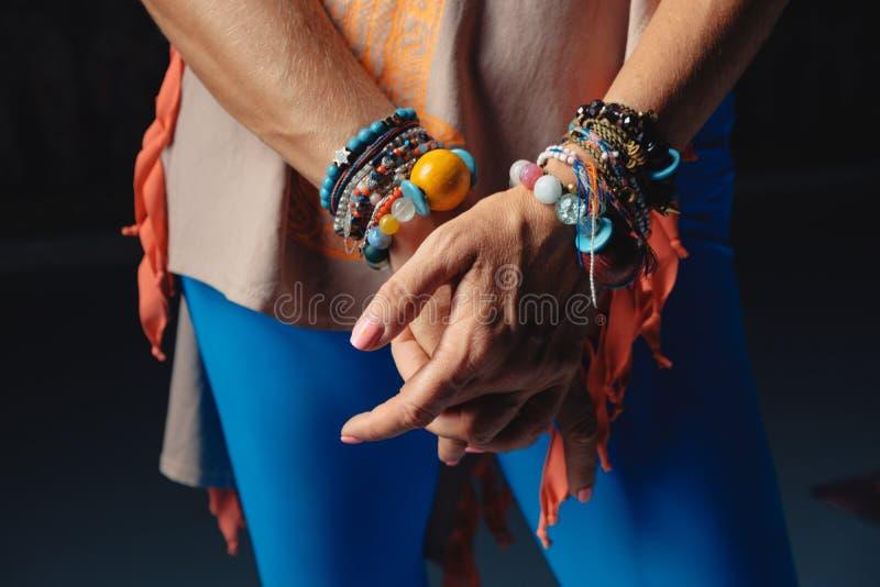 Händer av den mogna kvinnan i färgrik tillbehör på handleder och colo arkivfoto