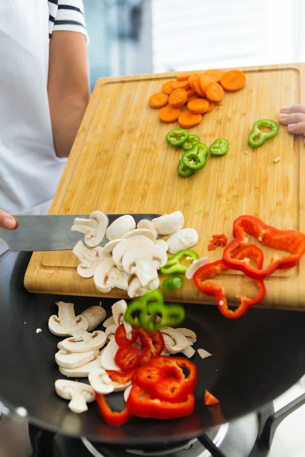 Händer av den sunda kvinnan som hemma sätter nya grönsaker i pannan i köket royaltyfri bild