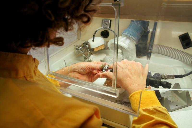 Händer av den tand- teknikeren som bearbetar muntlig protes för metall royaltyfri foto