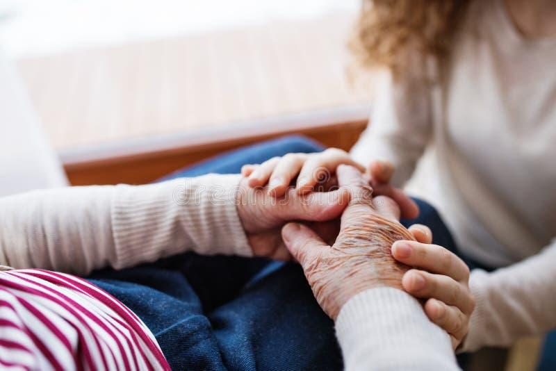 Händer av den tonårs- flickan och hennes farmor hemma royaltyfria bilder