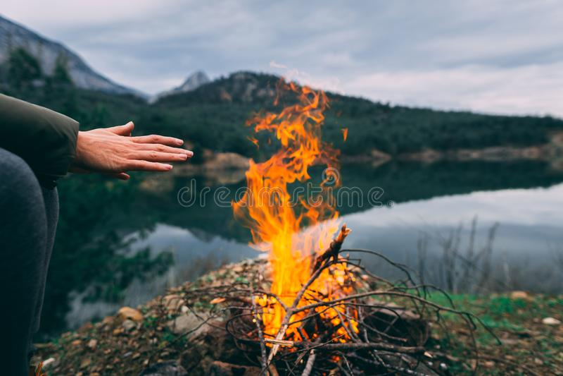 Händer av den unga kvinnan som värmer upp vid lägerbrand royaltyfri bild