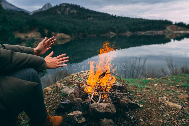 Händer av den unga kvinnan som värmer upp vid lägerbrand arkivbild