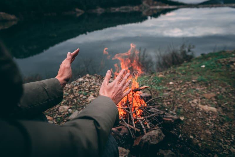 Händer av den unga kvinnan som värmer upp vid lägerbrand fotografering för bildbyråer