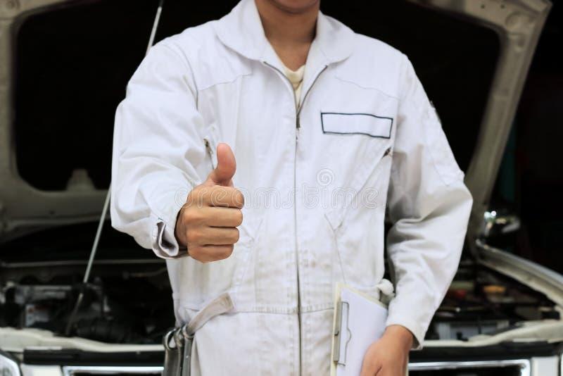 Händer av den yrkesmässiga unga mekanikermanvisningen tummar upp som tecken av framgång med bilen i öppen huv på garagebakgrunden arkivbild