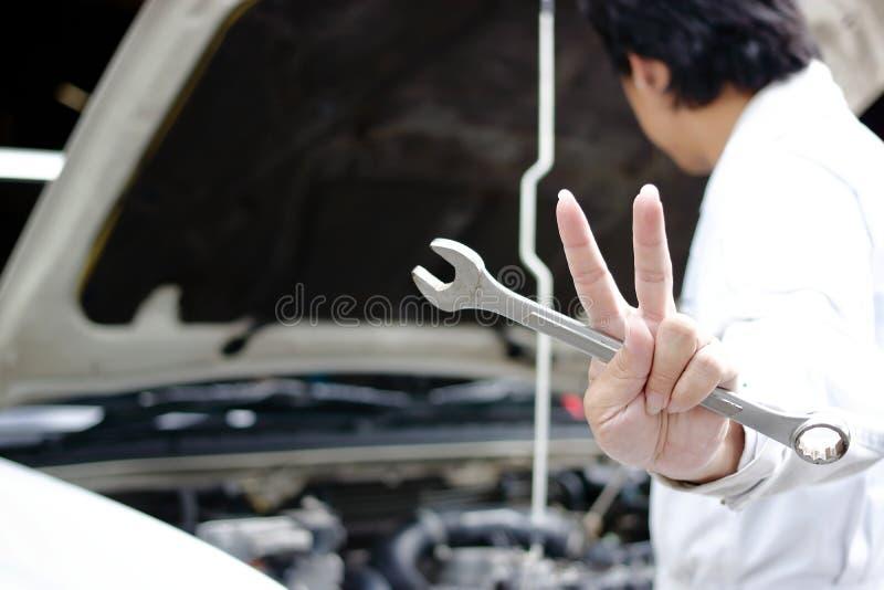 Händer av det säkra unga mekanikerinnehavet rycker häftigt, och att lyfta två fingrar upp den är shower slåss med jobb mot bilen  royaltyfri foto