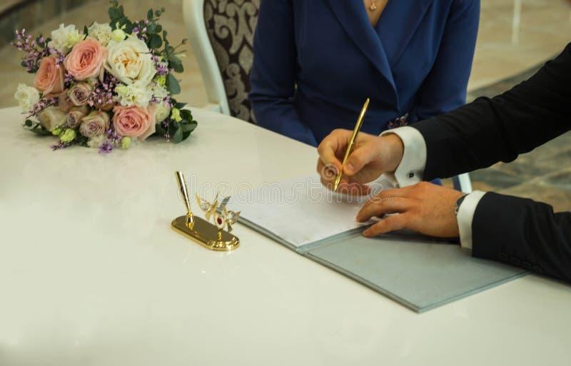 Händer av det undertecknande förbindelseavtalet för brudgum och den brud- buketten, selektiv fokus royaltyfria foton