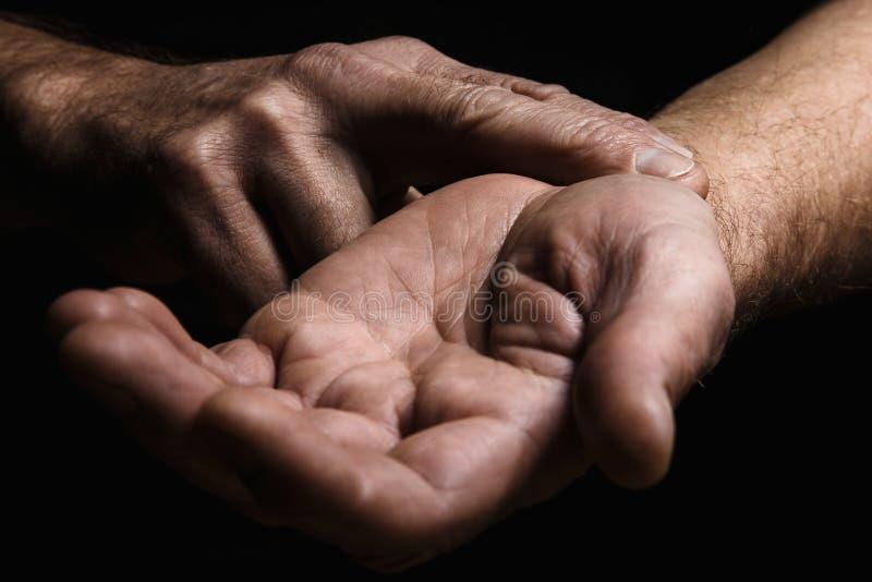 Händer av en äldre man med två fingrar som mäter pulsen Lo arkivbilder