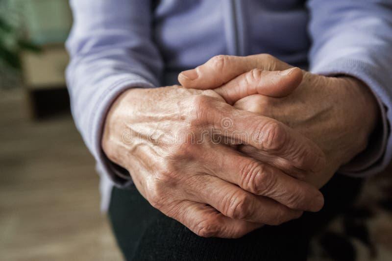 Händer av en äldre person Rynkig handfarmor arkivbild