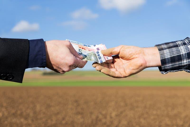 Händer av en affärsman och en bonde med en pengaröverföring royaltyfria foton