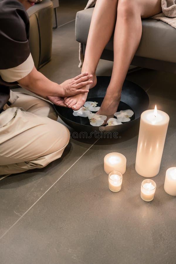 Händer av en asiatisk terapeut under fottvagningbehandling arkivbild