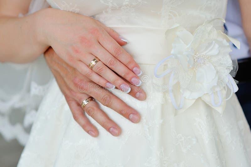 Händer av en brud och en brudgum med guldbröllopcirklar arkivfoto