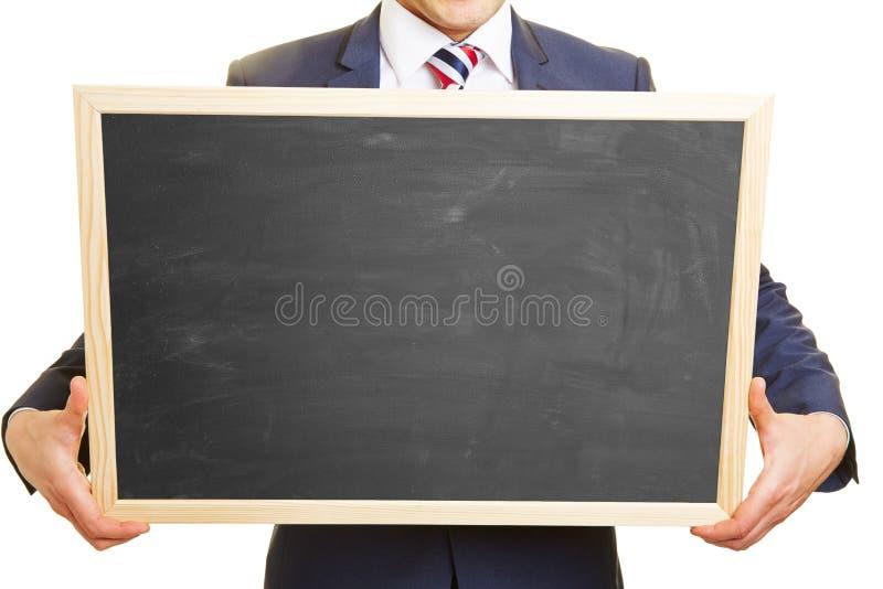 Händer av en chef som rymmer den tomma svart tavla royaltyfri foto