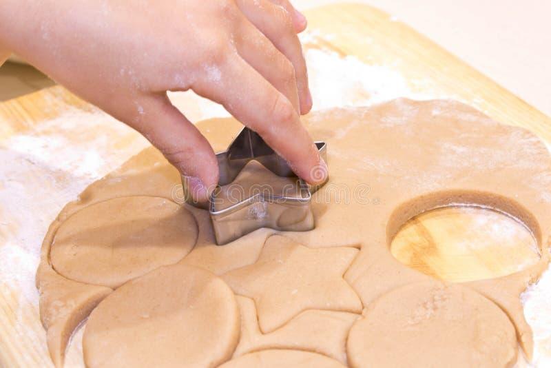 Händer av en flicka med deg som lagar mat kakor på en trätabell close upp royaltyfri bild