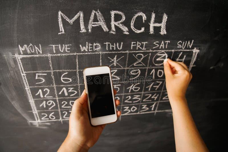 Händer av en flicka med en smartphone på bakgrunden av kalendern som är skriftlig på väggen av en mörk svart tavla royaltyfri bild