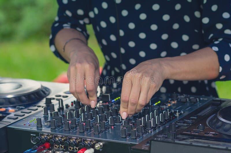 Händer av en flicka som spelar en närbild för discjockeyblandarekonsol royaltyfri fotografi