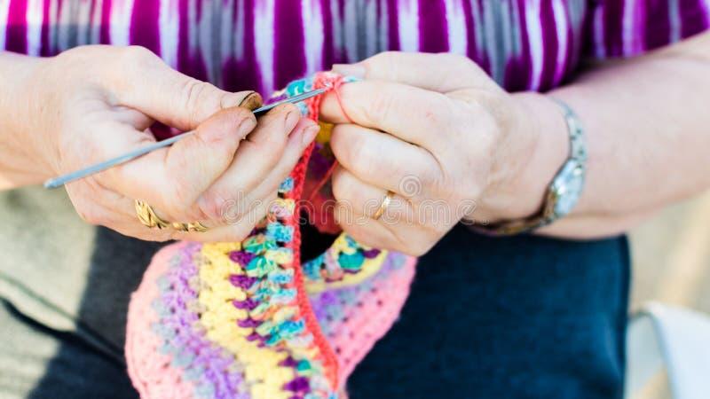 Händer av en gammal dam som sticker på stickor, genom att använda färgrik ull arkivbild