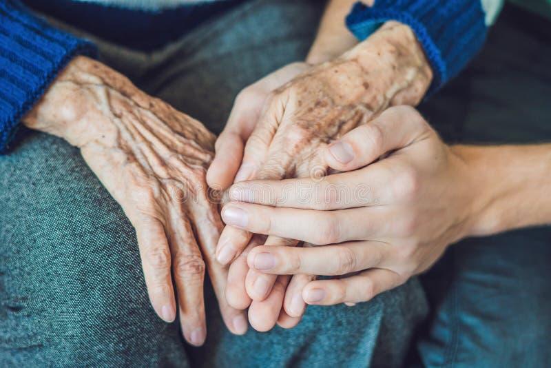 Händer av en gammal kvinna och en ung man Att bry sig för åldringen C royaltyfria foton