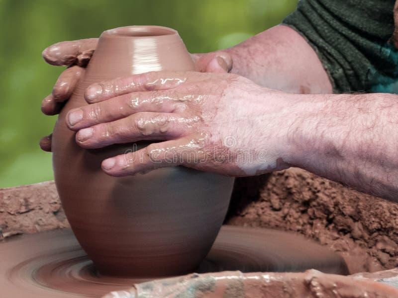 Händer av en keramiker gör en skyttel med en smal hals royaltyfria bilder