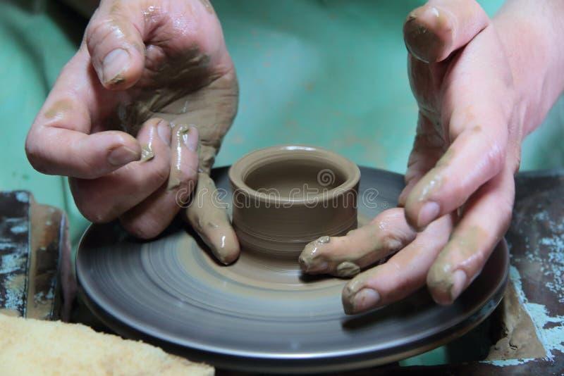 Händer av en keramiker som skapar en jord- krus på krukmakerihjulet royaltyfri bild