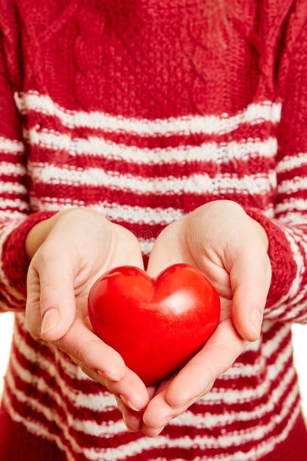 Händer av en kvinna som rymmer en röd hjärta av förälskelse arkivfoton