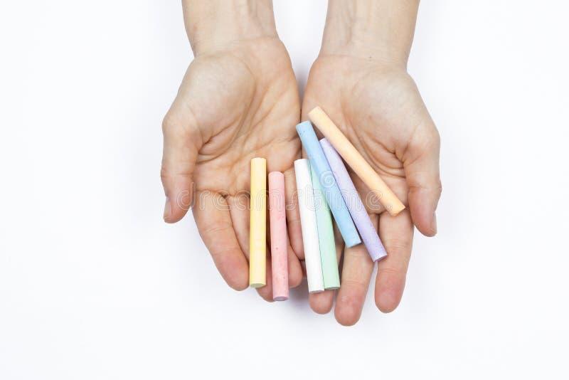 Händer av en kvinna som rymmer några kulöra chalks arkivbild