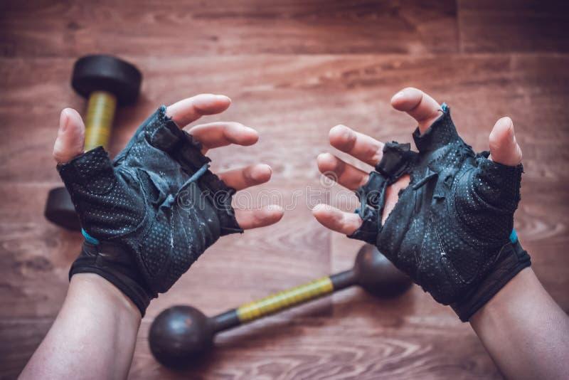 Händer av en man i sönderrivna sporthandskar royaltyfria bilder