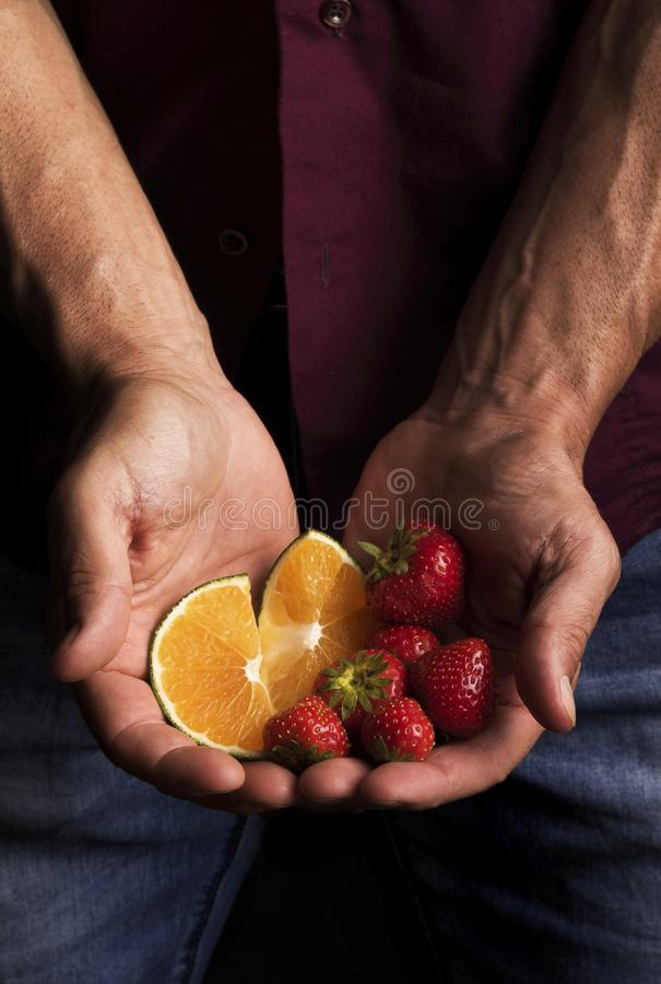 Händer av en man som rymmer frukt arkivfoton