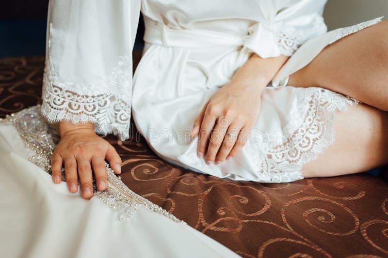 Händer av en ung kvinna lägger på hennes ben, henne sitter på stolen arkivbilder