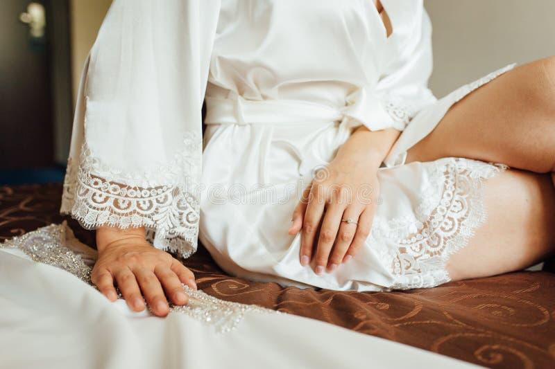 Händer av en ung kvinna lägger på hennes ben, henne sitter på stolen arkivfoto